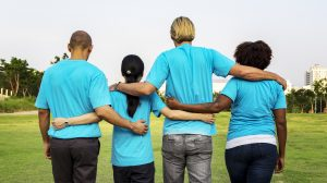 An image of four young people in blue t-shirts in the countryside demonstrating inclusion at university