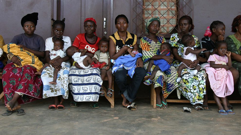 women holding children outside poliovirus vaccination clinic in Africa