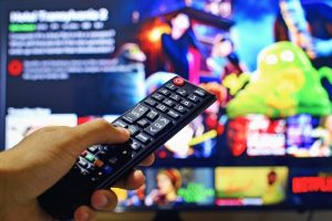 Can cinema survive in an online streaming world? [Person holding remote to television, showing Netflix]